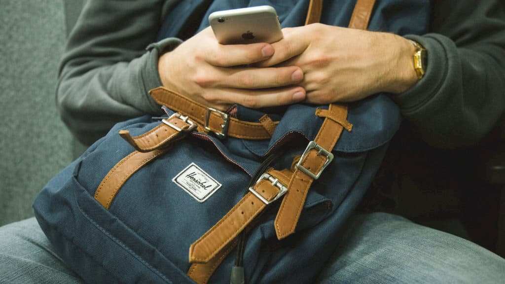 A person holding on to their Herschel bag and cell phone