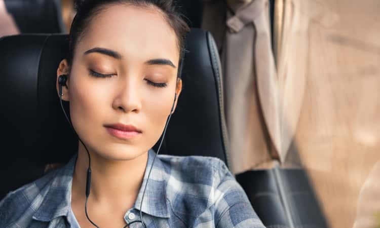 a woman sleeping on a charter bus with headphones on