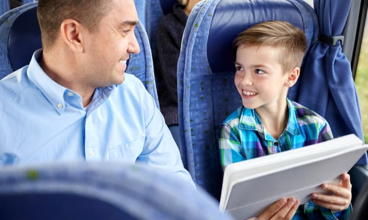 a man and young boy doing homework on a charter bus