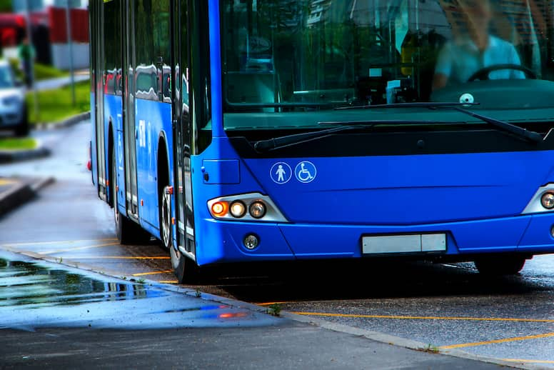 a blue charter bus approaches interstitial space on the road