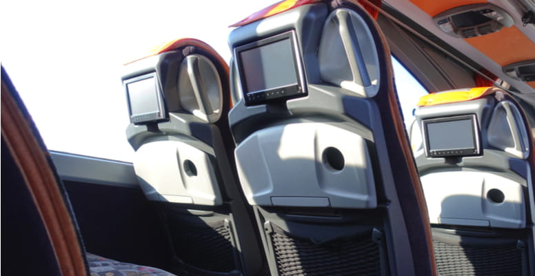 a row of charter bus seats with television screens built-in behind the headrests