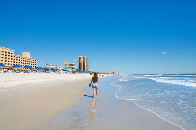 a woman walks along the shore of one of jacksonville's beaches