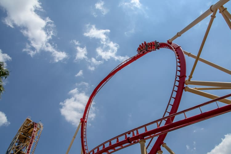 a view of a tall loop on a red rollercoaster at universal orlando