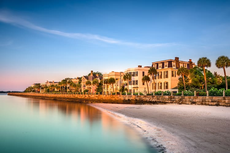 old classic homes on the shore of charleston next to calm waters at dusk