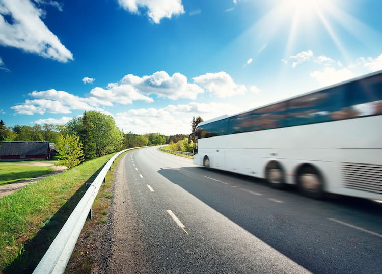 a white charter bus zooms down an open road towards a curve with a blue, cloudy sky in the background