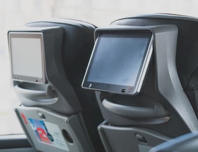 Inside of a charter bus with tvs in the seat backs