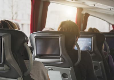 Inside of a charter bus people watching tv