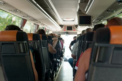 Rows of charter bus seats with people riding