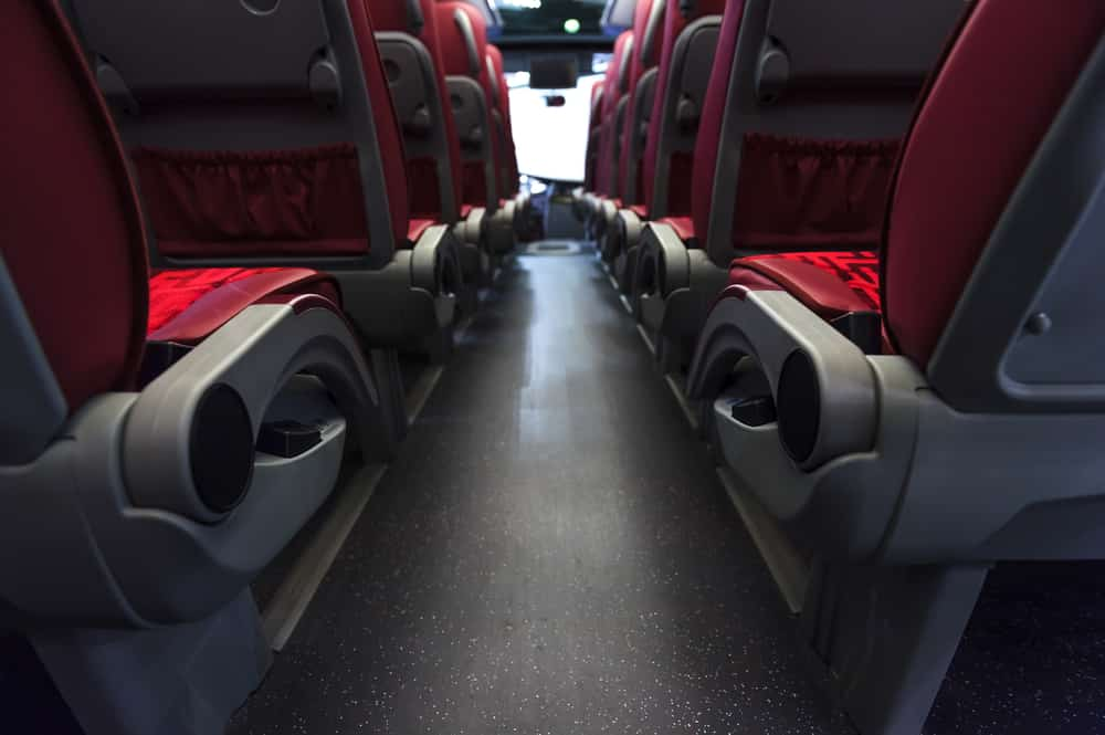 View from rear of red and gray charter bus seats