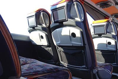 Rear view of charter bus seats with tv screen and cup holders