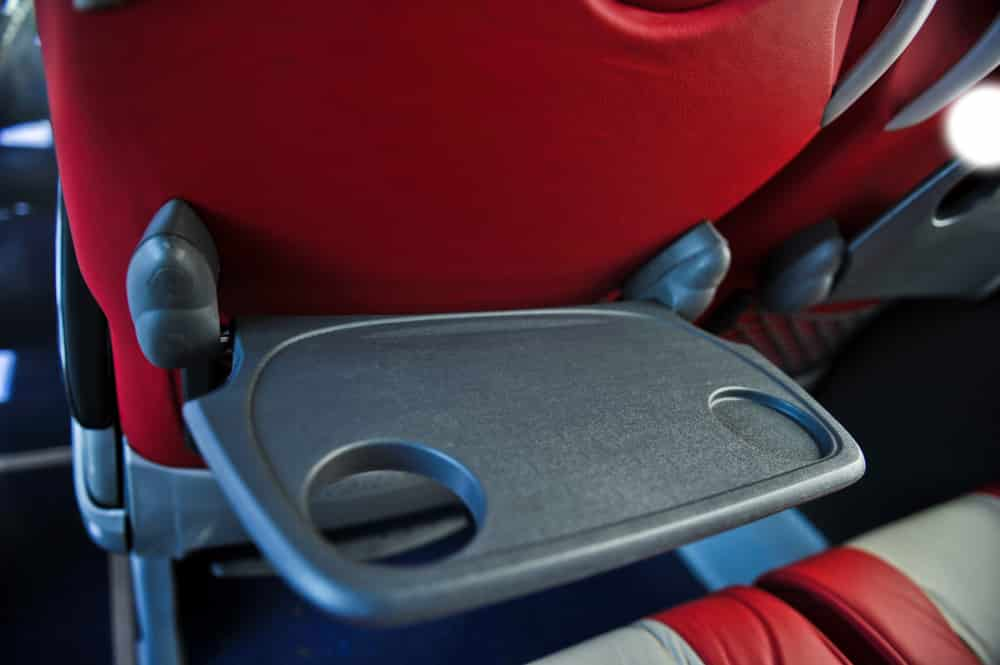 Red charter bus seat with gray tray table