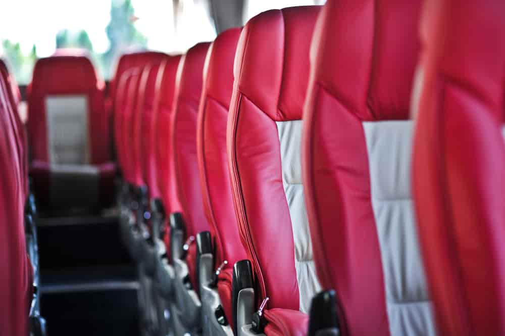 Rows of red and gray charter bus seats