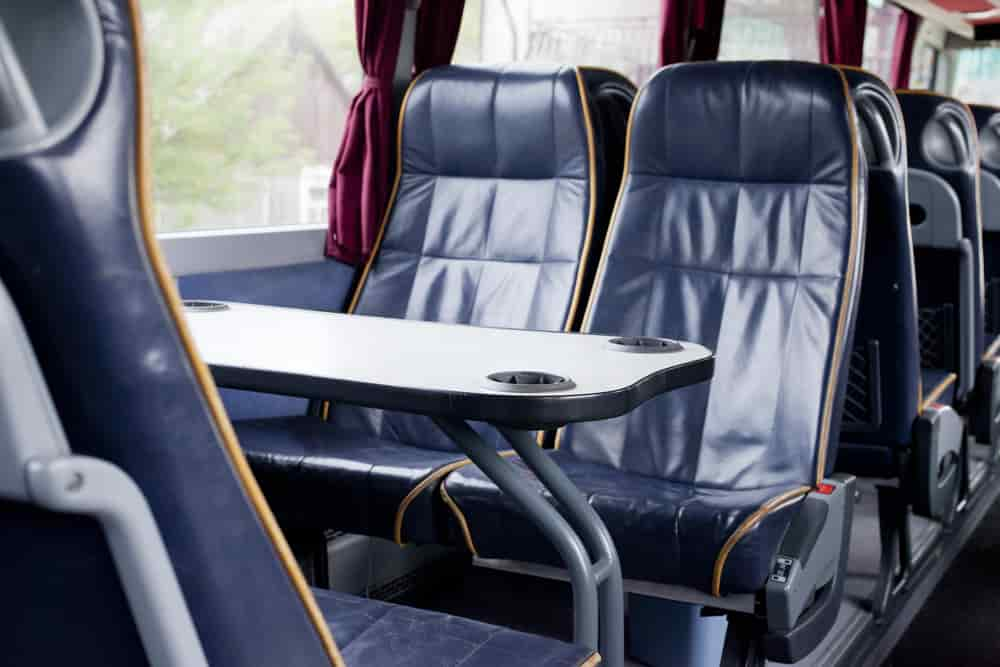 Black charter bus seats with large tray tables