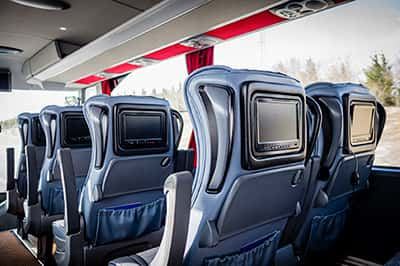 Sleek blue charter bus seats with tv screens in the backs