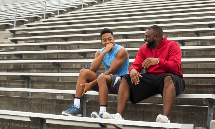 Two athletes laugh and talk in the stands of a stadium after practice