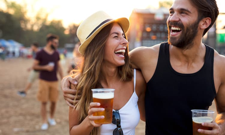 Two people enjoying beers at a music festival