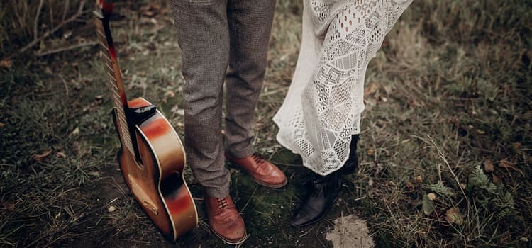 A couple taking wedding photos with a guitar and cowboy boots.