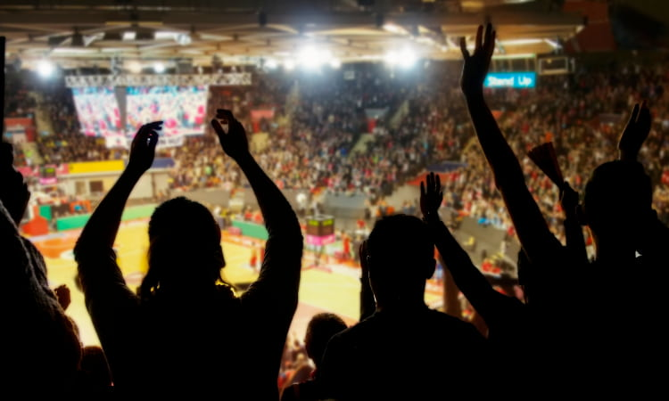 Basketball fans cheer with their arms up in dark stadium stands