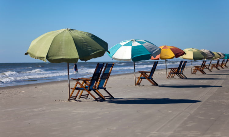 A lineup of empty beach chairs and umbrellas on a Galveston, Texas beach