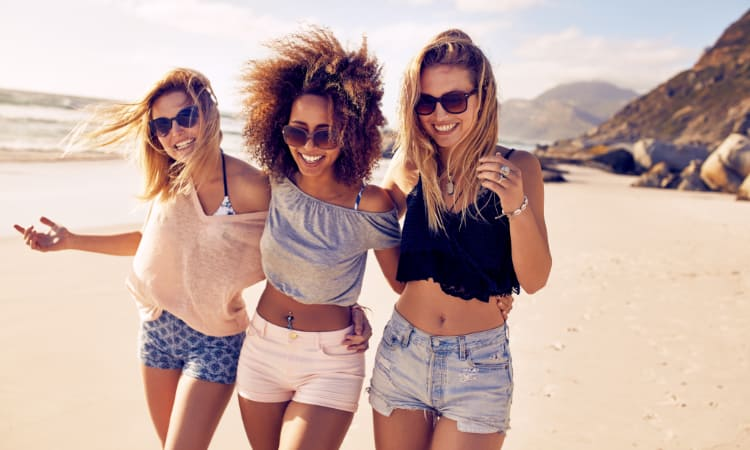 A group of three friends walk on a beach and laugh