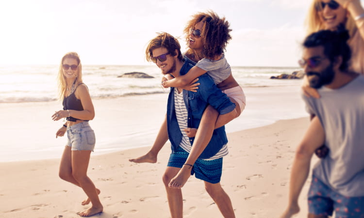 A gorup of young adults walk along a beach and laugh, some giving each other piggyback rides