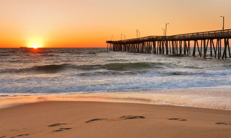 The sun sets over the pier and beach at Virginia Beach