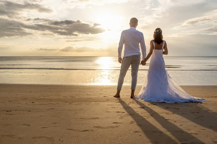 Bride and groom on beach looking at water