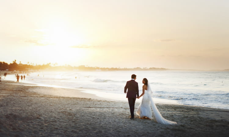 A bride and groom walk on the beach while holding hands