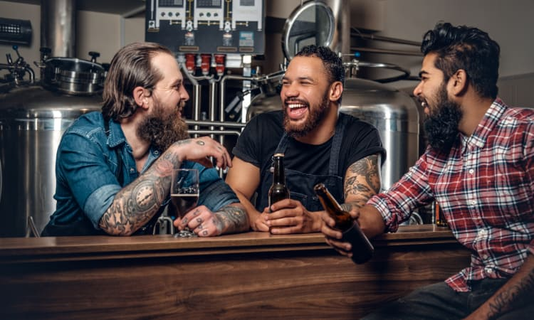 A group of tattooed friends drink beers in a brewery