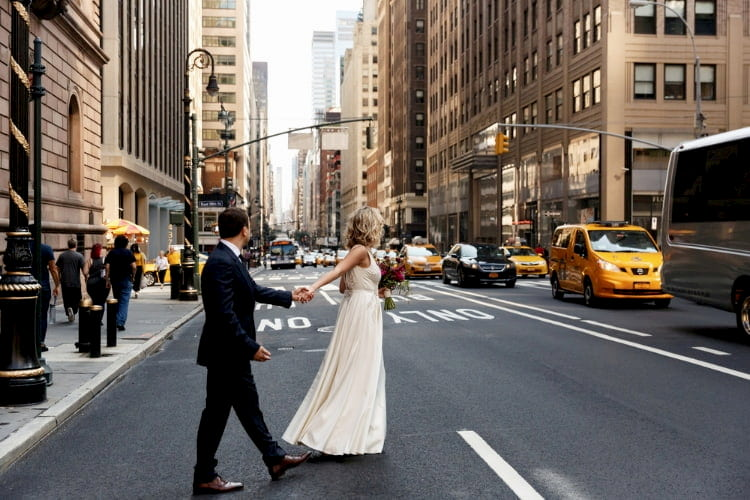 A bride and groom hold hands and cross a busy New York City street
