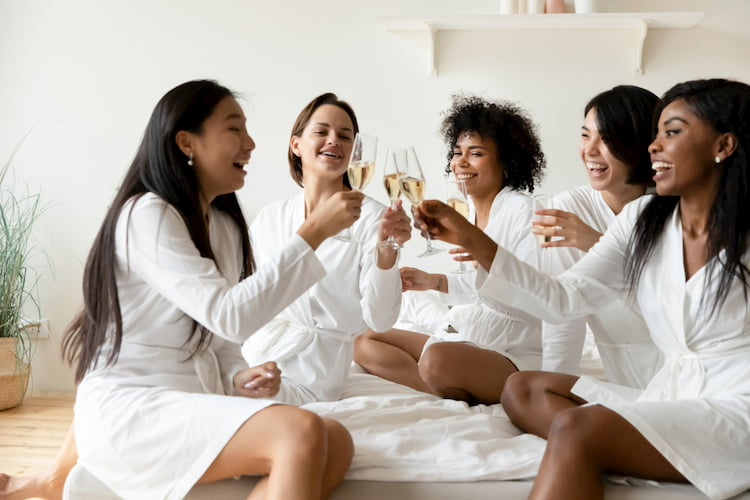 Bridesmaids and bride in bathrobes with champagne