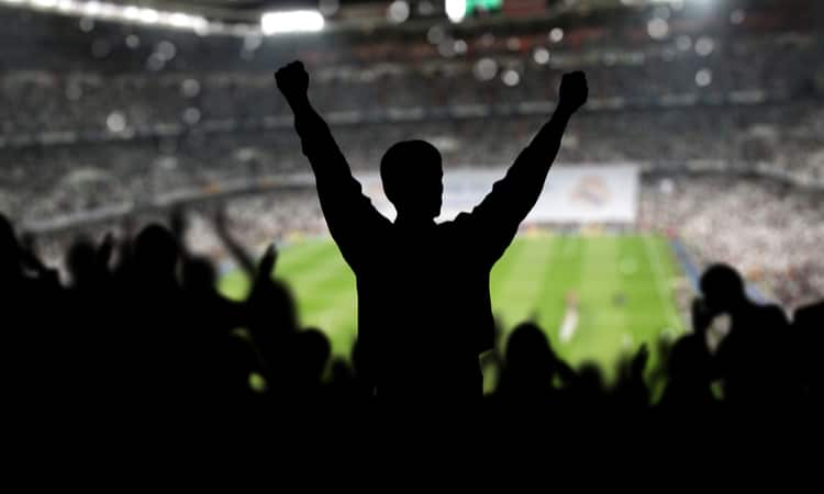 A group of sports fans cheering in a stadium