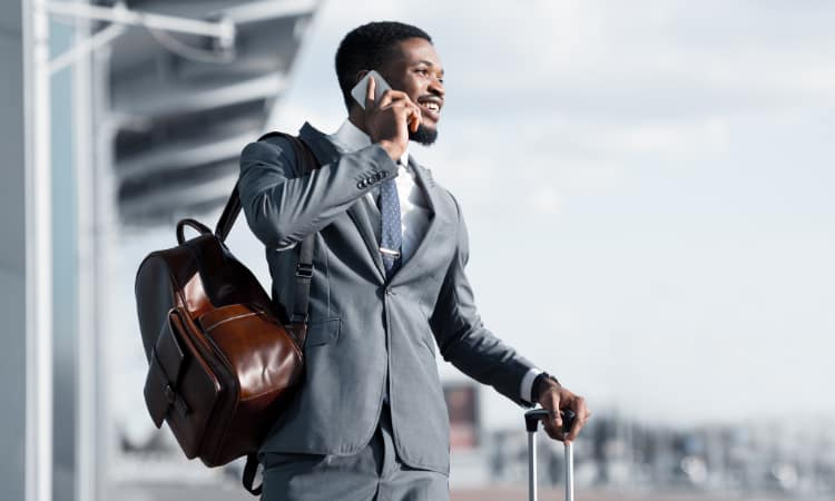 A businessman waits for his shuttle service while talking on the phone