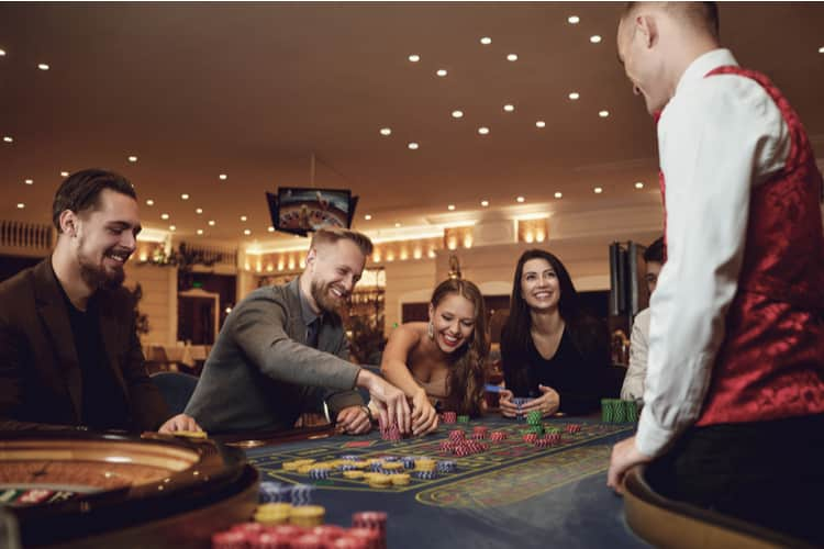 A group of people at a roulette poker in a casino