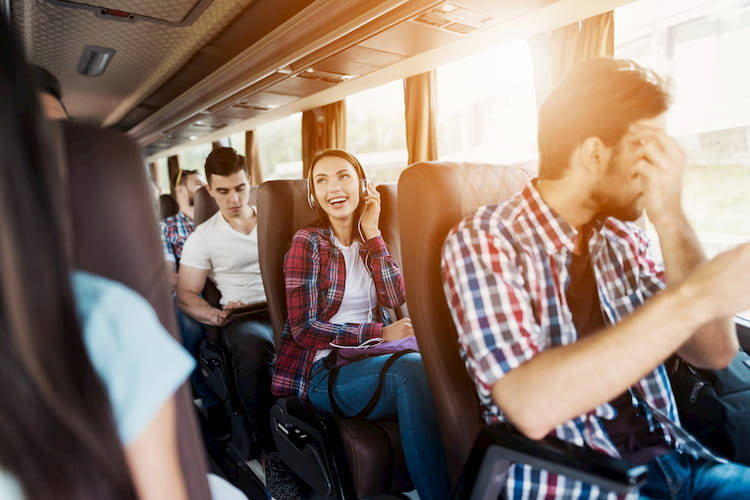 Woman sitting on bus in headphones and listening to music next to other people who also went on a trip.