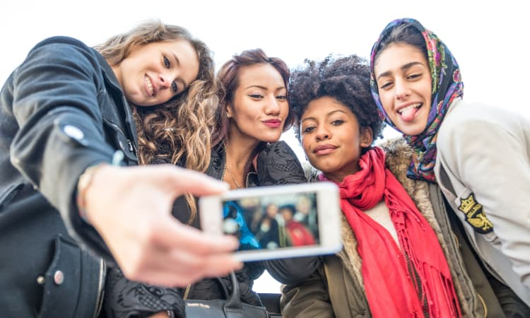 A group of students pose for a selfie after a college tour