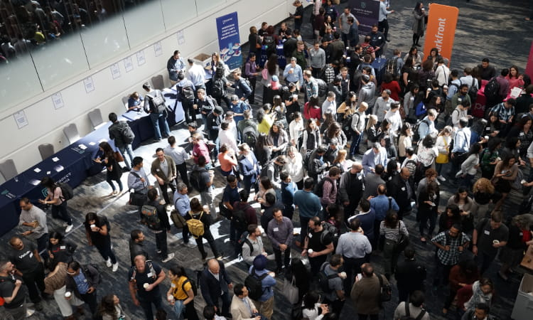 a crowd of conference attendees network in a conference center