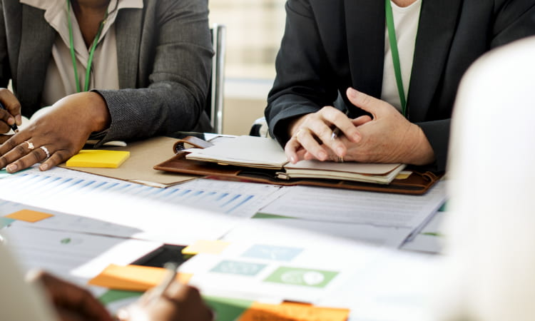 A closeup of paperwork and hands of employees during a business meeting at a conference table