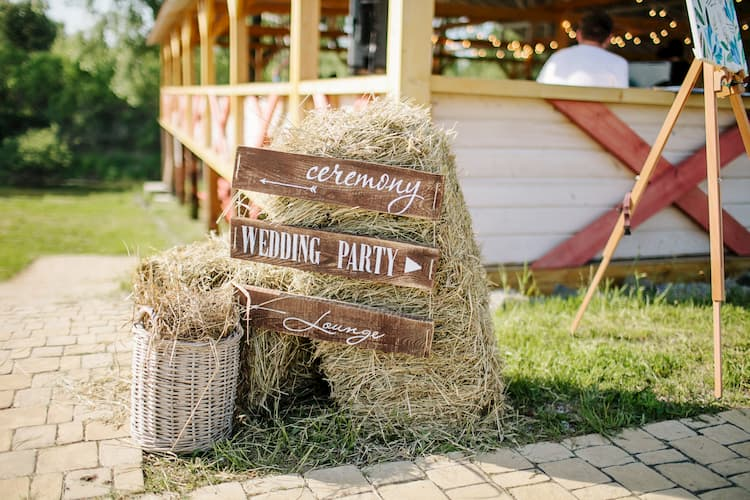 a country sign propped up hay bales pointing to a wedding ceremony