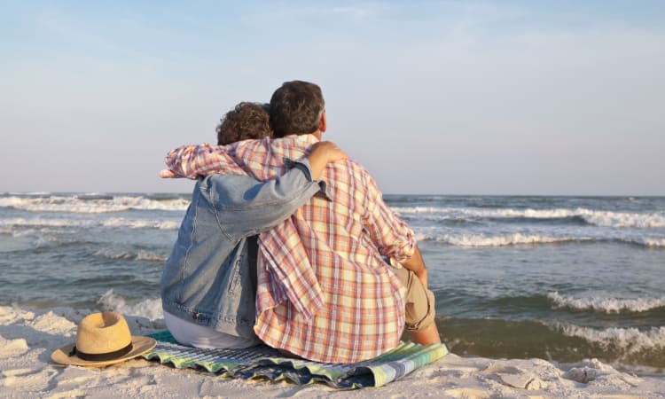 A mature couple sit on a blanket on the beach, arms around each other and watching the waves