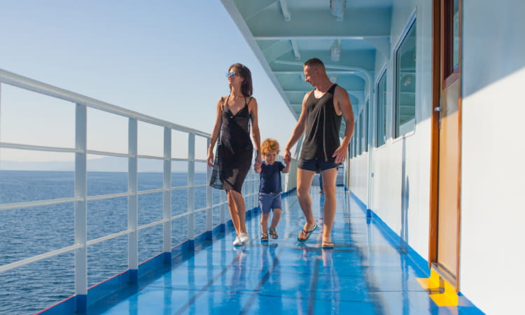 A mother, father, and a toddler walk on the deck of a cruise ship, admiring the open ocean