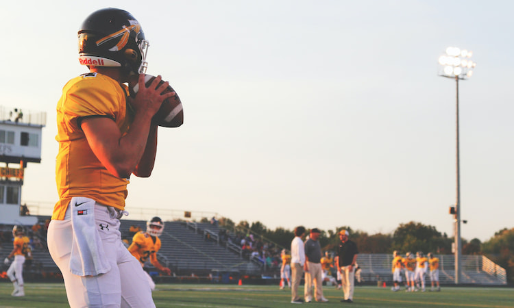 A football quarterback prepares to pass a football in a high school stadium