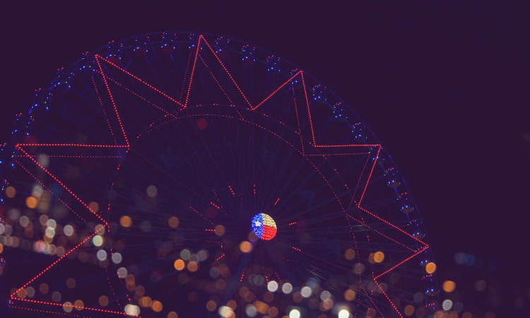 Texas Star Ferris Wheel at night, with bokeh lights at its base
