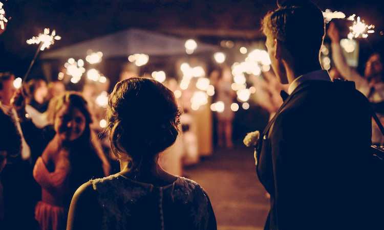 a young bride and groom at their wedding reception, guests with sparklers in the background