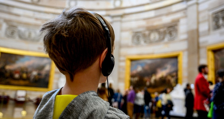 a child wears headphones and listens to a guided audio tour in the U.S. Capitol Building