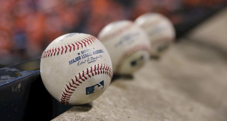 a lineup of 3 baseballs in a Major League dugout