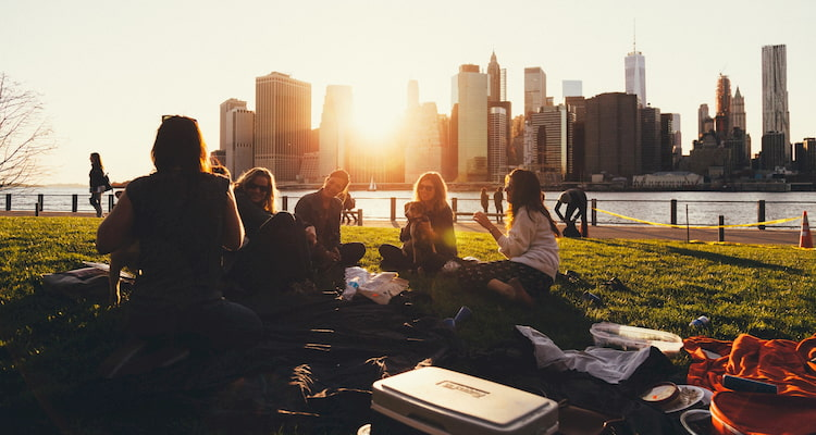 a group of friends relax at a riverside park at sunset, the New York City skyline in the background