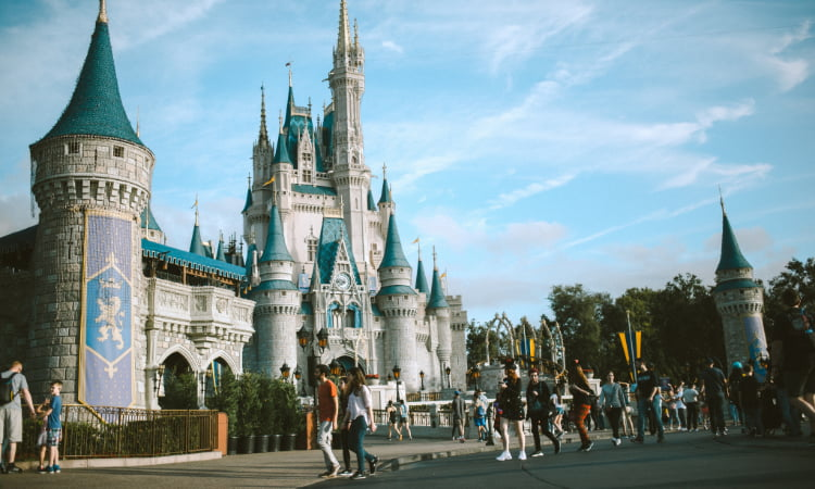 crowds enter Disney World, with the castle prominent in the background