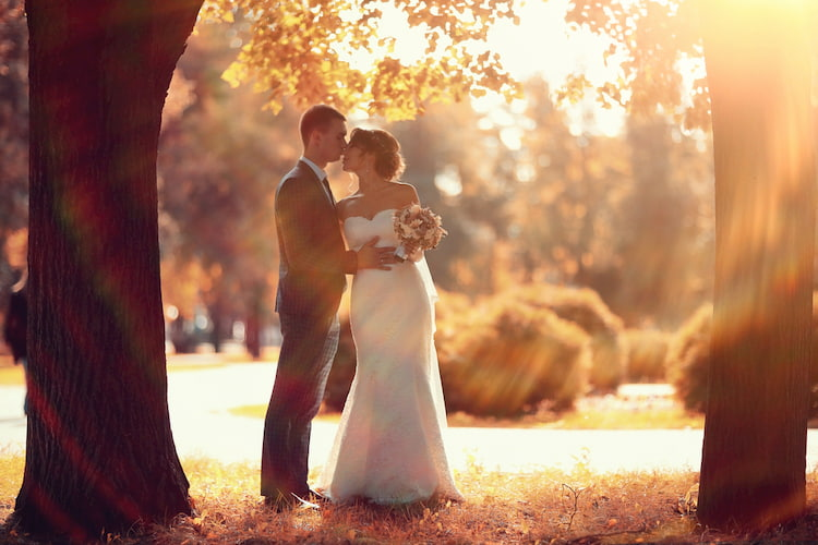 Newlywed groom and bride walking in autumn park