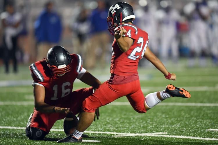 A football player sets up a kick for a quarterback at a Texas football game